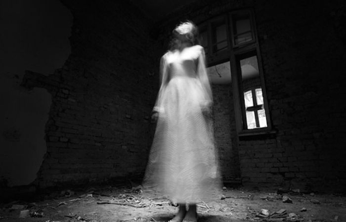 Ghost girl in white dress in ruined house