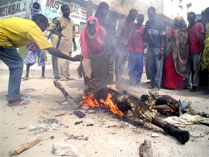 ** EDS NOTE GRAPHIC CONTENT ** Somali's gather around the smoldering body of a Somali goverment soldier after he was killed during heavy fighting in the Somali capital, Mogadishu, Wednesday, March 21, 2007.Somali and Ethiopian troops entered an insurgent stronghold in central Mogadishu on Wednesday, triggering a battle in which at least seven people were killed and 10 were injured, witnesses and medical officials said.(AP Photo/Str)